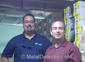 Mike Scott (left) is featured in tonight's premeire episode of Dig Wars on the Travel channel. Pictured to the right of Mike is longtime friend Daniel Bernzweig. The two are pictured in front of one of the aisles of Fisher metal detectors in the MetalDetector.com warehouse in Southborough, MA.